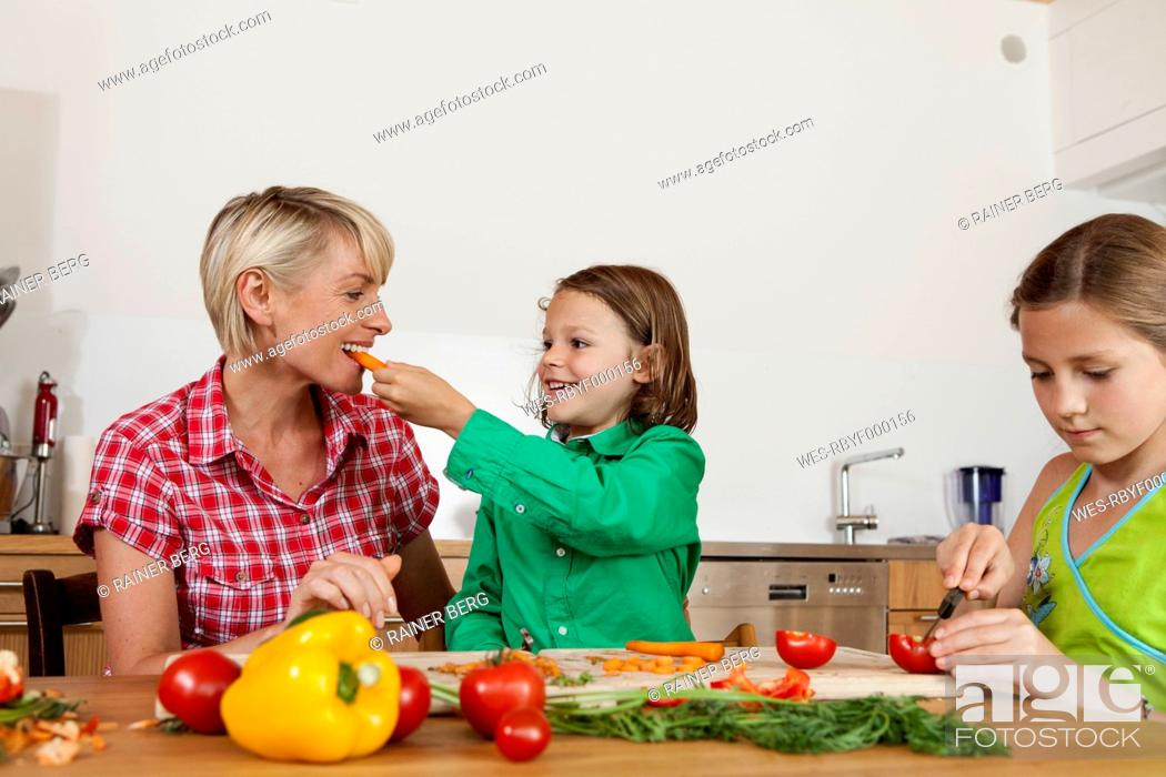 Stock Photo: Germany, Bavaria, Nuremberg, Mother and children cutting vegetables.