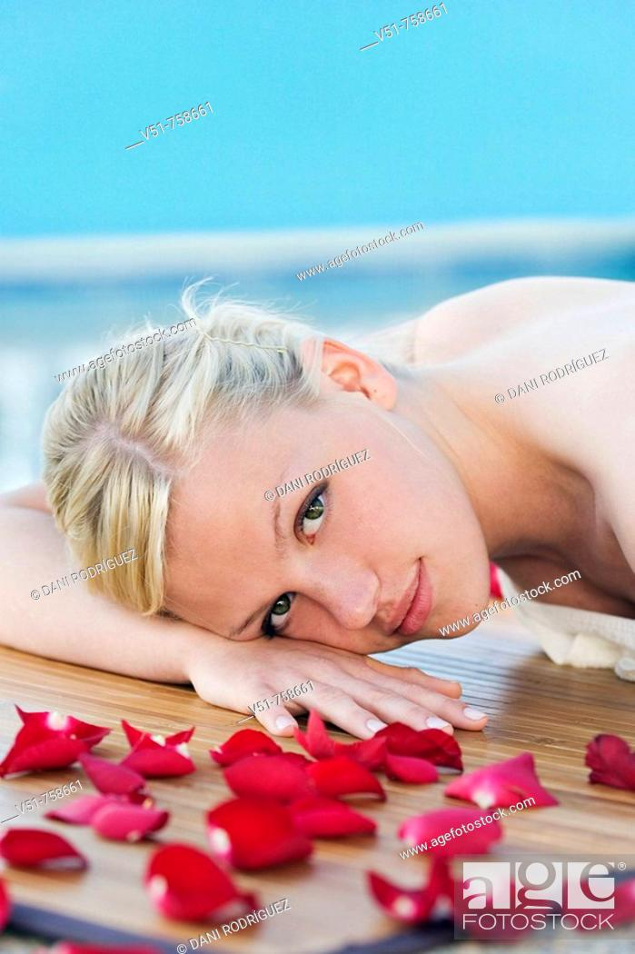 Stock Photo: Young woman having a massage by the pool.