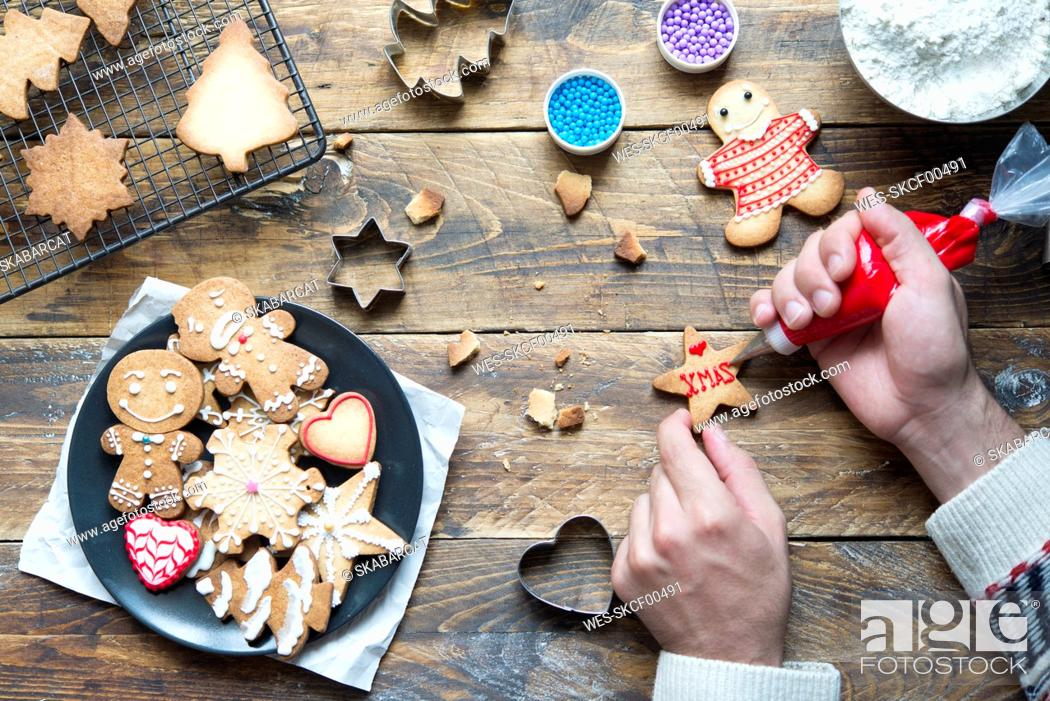 Stock Photo: Man's hand decorating Christmas cookie.