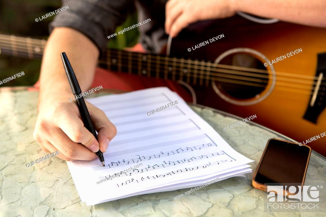 Stock Photo: Close up of young man composing music.