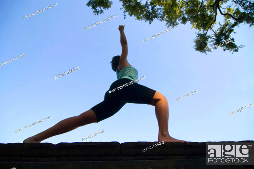 Stock Photo: Silhouetted young woman exercising.