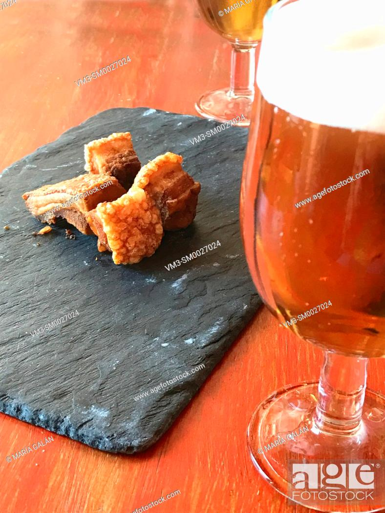 Stock Photo: Glass of beer and torreznos serving. Spain.