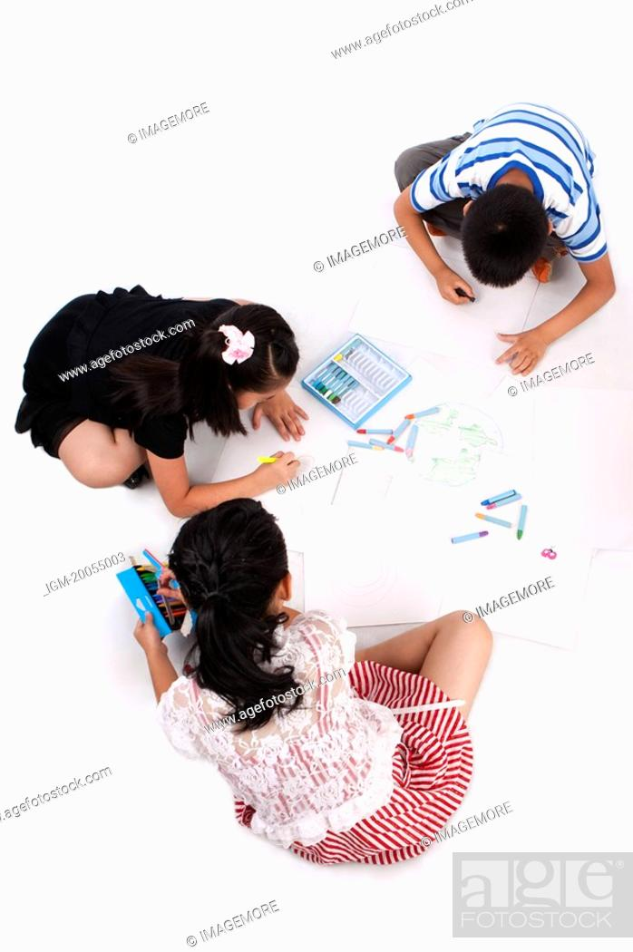 Photo de stock: Child, Three children sitting and drawing on the floor together.