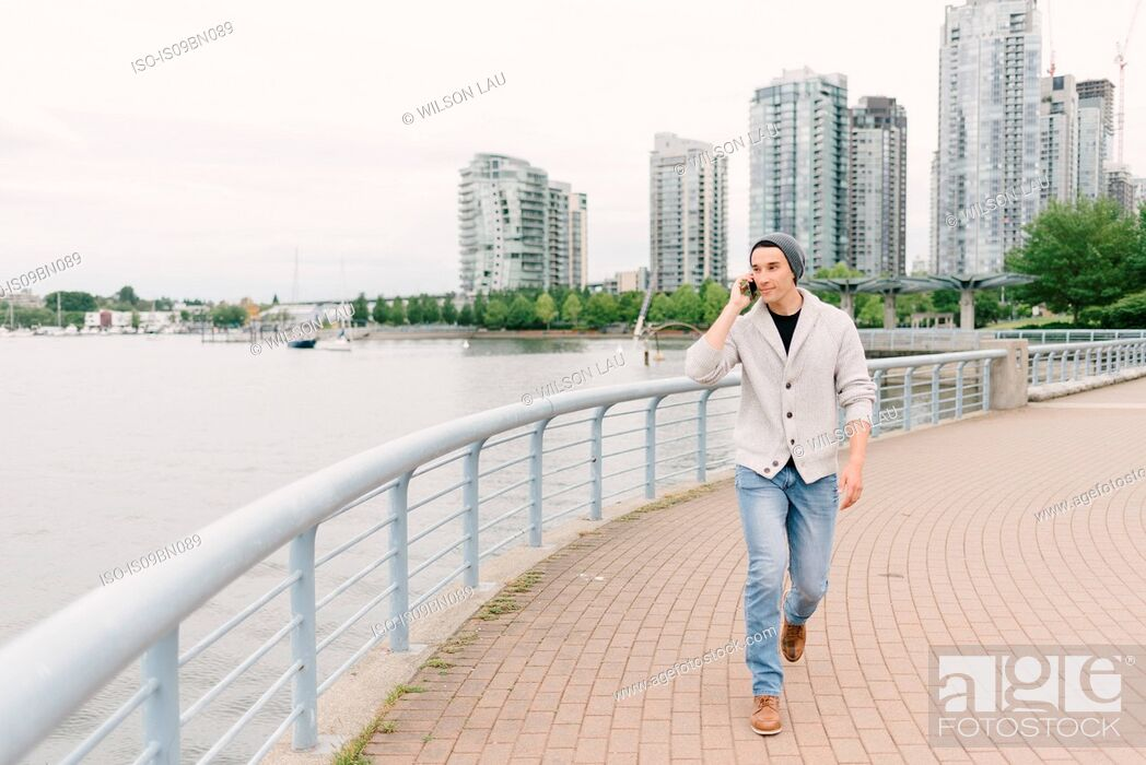 Photo de stock: Young man talking on phone while walking along seawall, Yaletown, Vancouver, Canada.