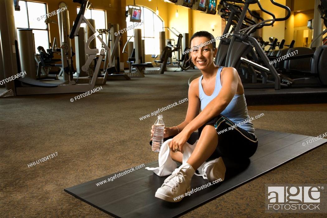 Stock Photo: Prime adult Caucasian female sitting on mat on gym floor.