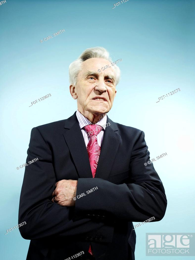 Stock Photo: An elegant senior man with his arms crossed looking displeased.