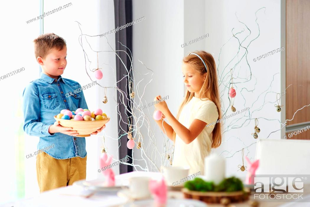 Stock Photo: Girl and brother decorating twigs with colourful easter eggs.