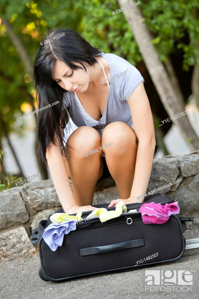 Stock Photo: Attractive young woman is packing a travel suitcase.