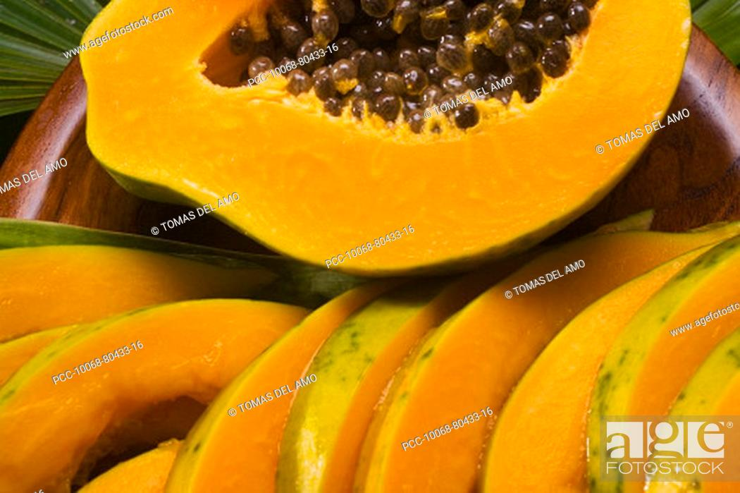 Stock Photo: Studio shot of papaya, halved and cut into slices.