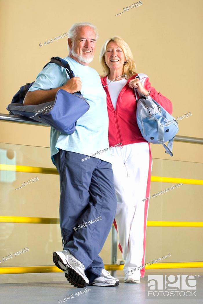 Stock Photo: Senior couple with gym bags, leaning against railing, smiling, portrait.