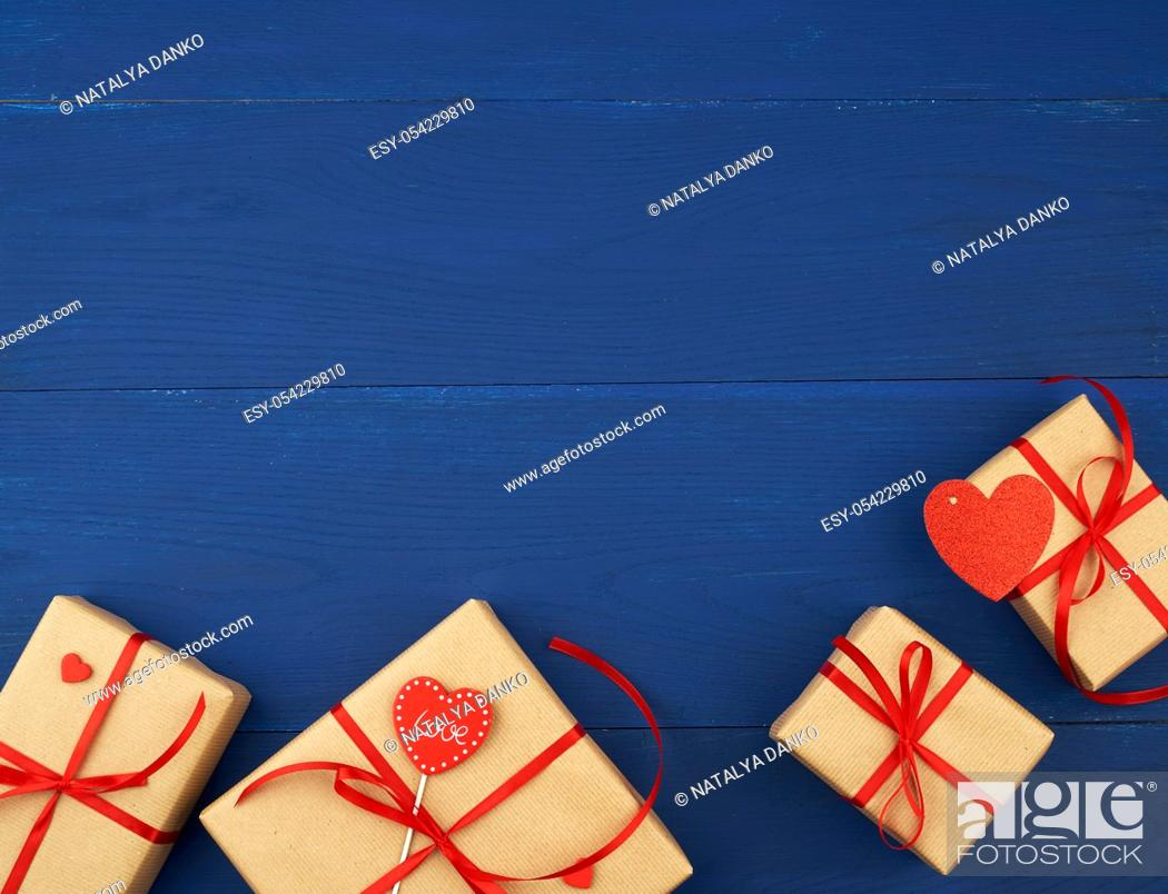 Stock Photo: brown box with a gift and a red paper heart, blue wooden background, top view, copy space.