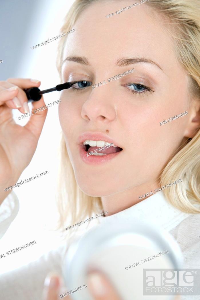 Stock Photo: woman applying mascara.