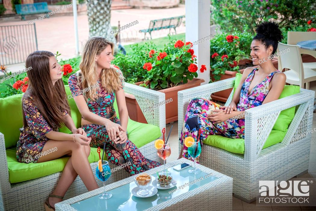 Stock Photo: Three young women relaxing on apartment patio talking, Costa Rei, Sardinia, Italy.