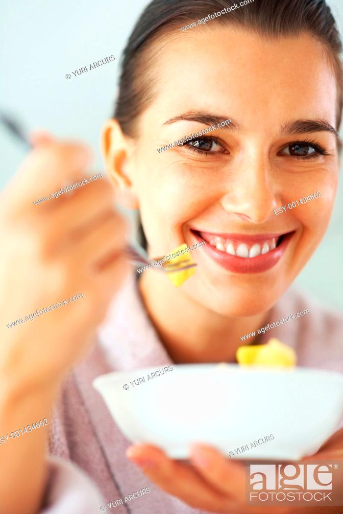 Stock Photo: Smiling woman with bowl of fruit.