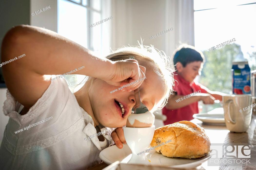 Stock Photo: Girl eating a boiled egg at dining table.
