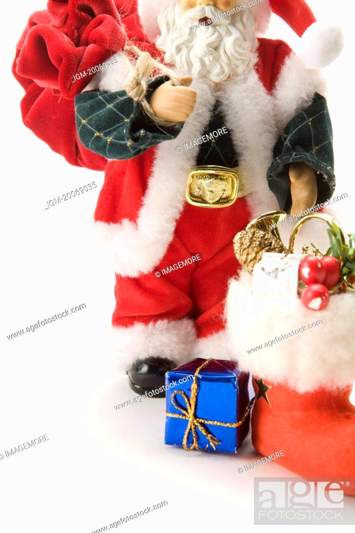 Stock Photo: Figurine of Santa Claus, carrying gifts and a bag.