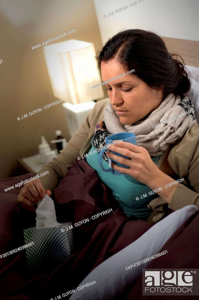 Imagen: Sick woman with cold flu in bed holding tissue and tea.