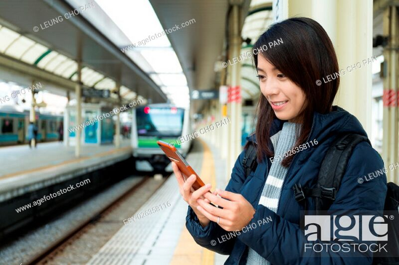 Stock Photo: Woman use of mobile phone at train station.