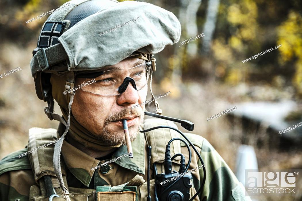 Stock Photo: Norwegian Armed Forces Special Command FSK soldier smoking cigarette closeup portrait. Radio and headset are on.
