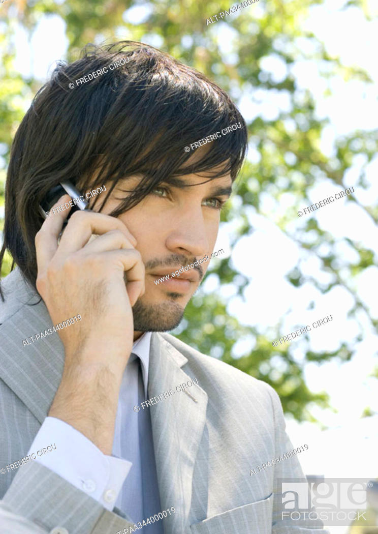 Stock Photo: Young businessman using cell phone.