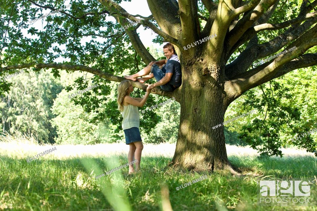 Stock Photo: A young woman talking to her boyfriend up a tree.