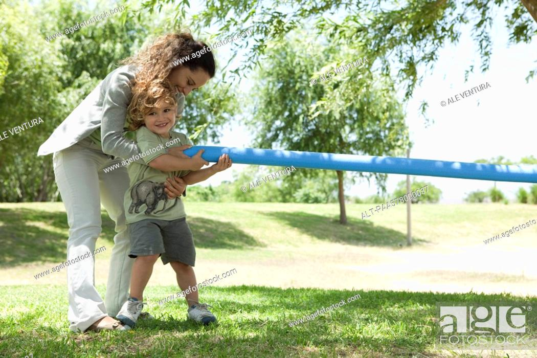 Stock Photo: Mother helping young son play tug-of-war.