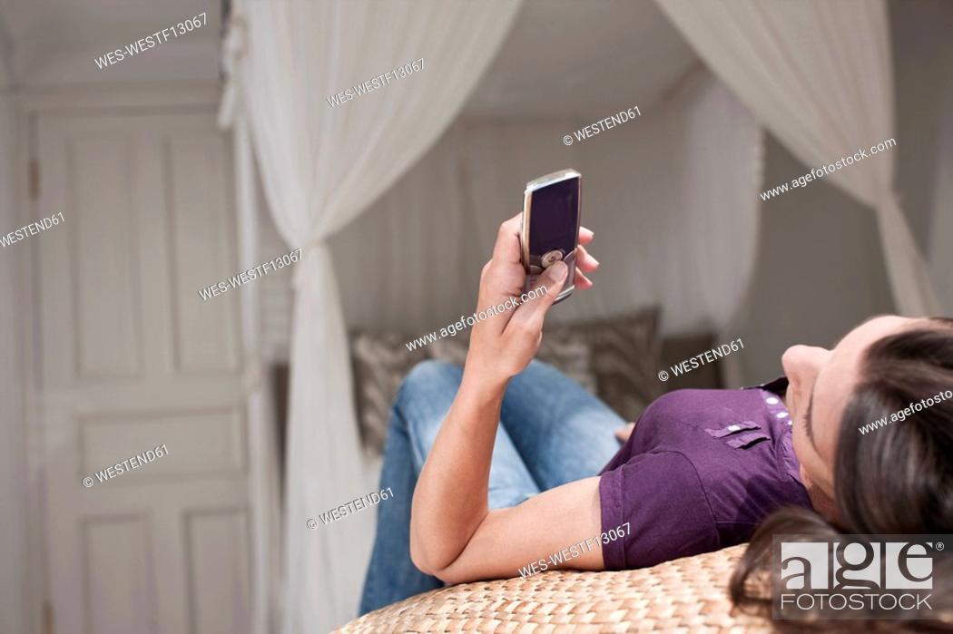 Stock Photo: Germany, Hamburg, Woman lying on bead reading SMS.
