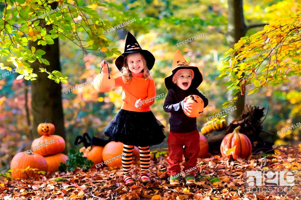 Stock Photo: Children wearing black and orange witch costumes with hats playing with pumpkin and spider in autumn Park on Halloween. Kids trick or treat.
