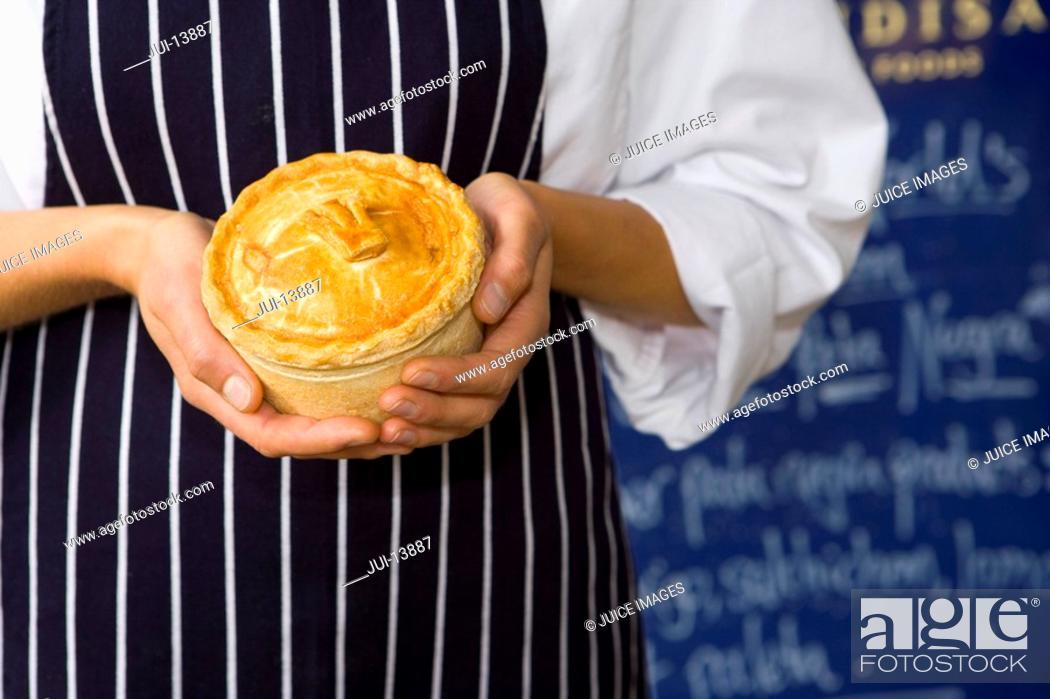 Stock Photo: Female baker with pie, mid section.