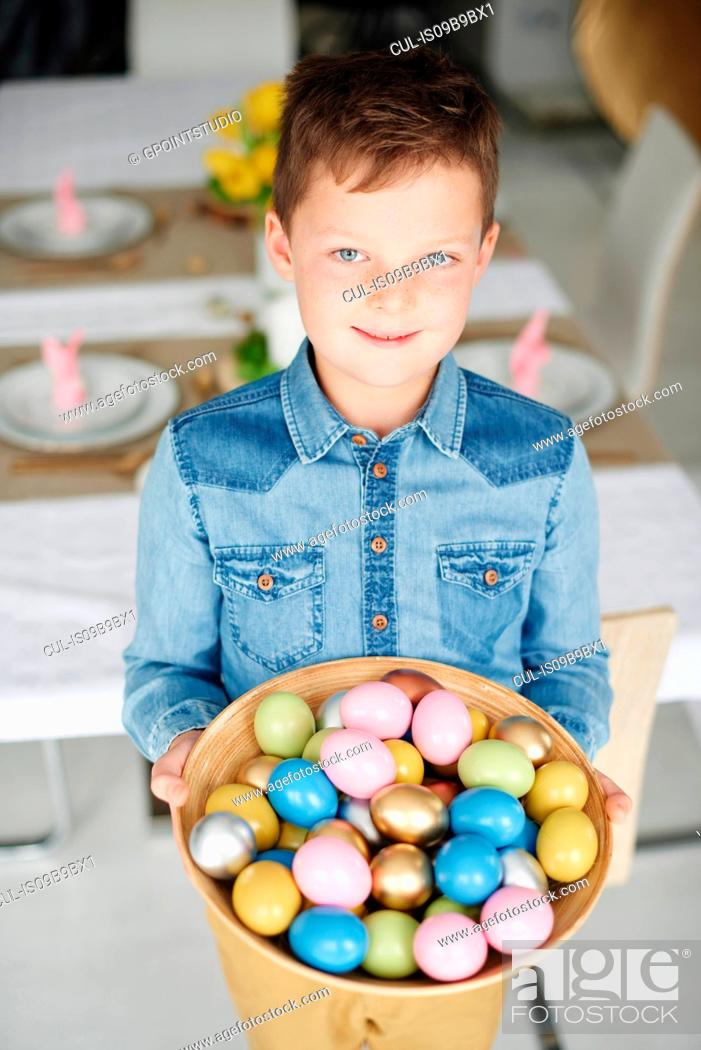 Stock Photo: Portrait of boy holding bowl of colourful easter eggs.