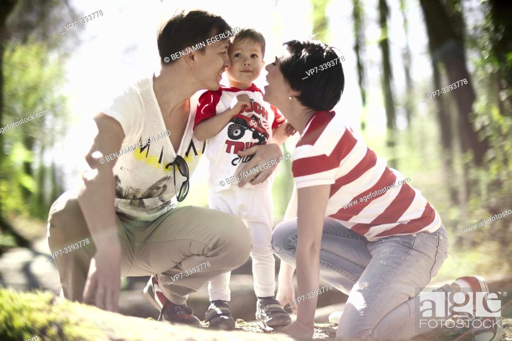 Stock Photo: toddler child with parents in forest, at Herrenchiemsee, Chiemsee, Bavaria, Germany.
