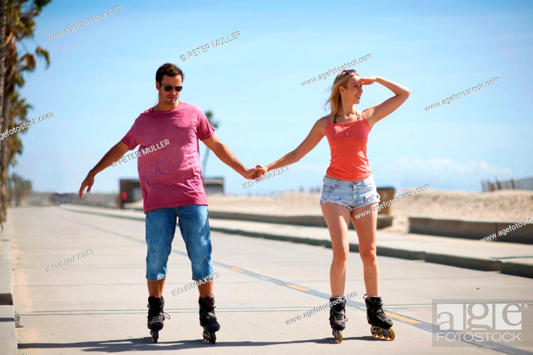 Stock Photo: Couple rollerblading outdoors, holding hands.