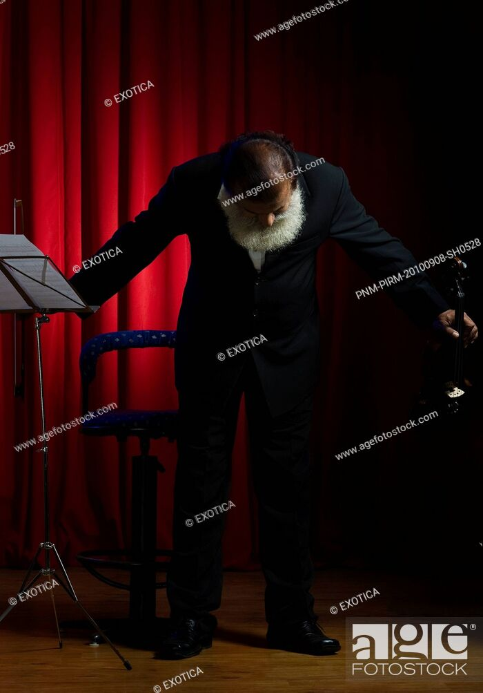 Stock Photo: Violinist taking a bow on stage after performance.