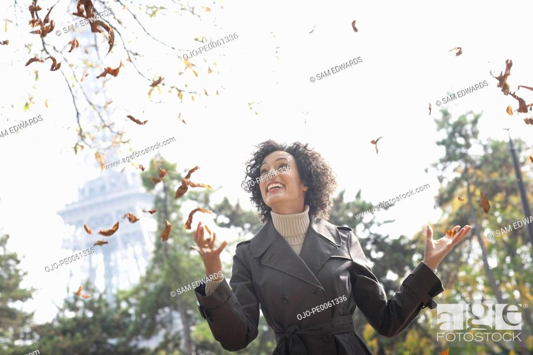 Stock Photo: Woman outdoors with falling leaves smiling.