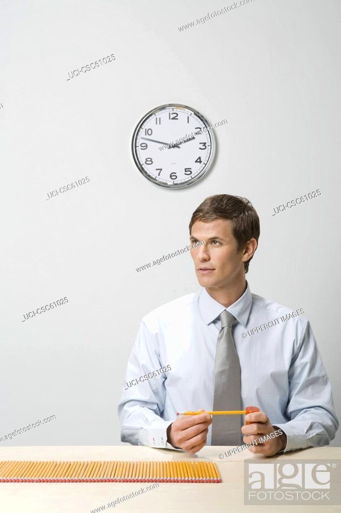 Stock Photo: Businessman next to row of pencils.