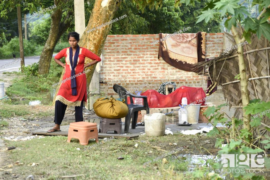 Stock Photo: A woman with her belongings in a safer place from flooded area, in Kamrup district of Assam, Monday, July 13, 2020.
