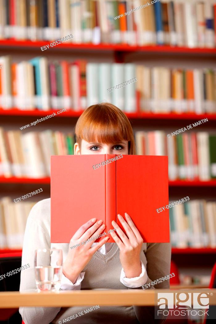 Stock Photo: Girl hiding behind the book on library.