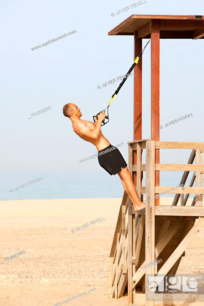 Stock Photo: man playing sports on the beach with trx.