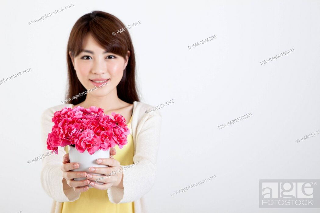Imagen: Young woman holding carnations and smiling at the camera,.