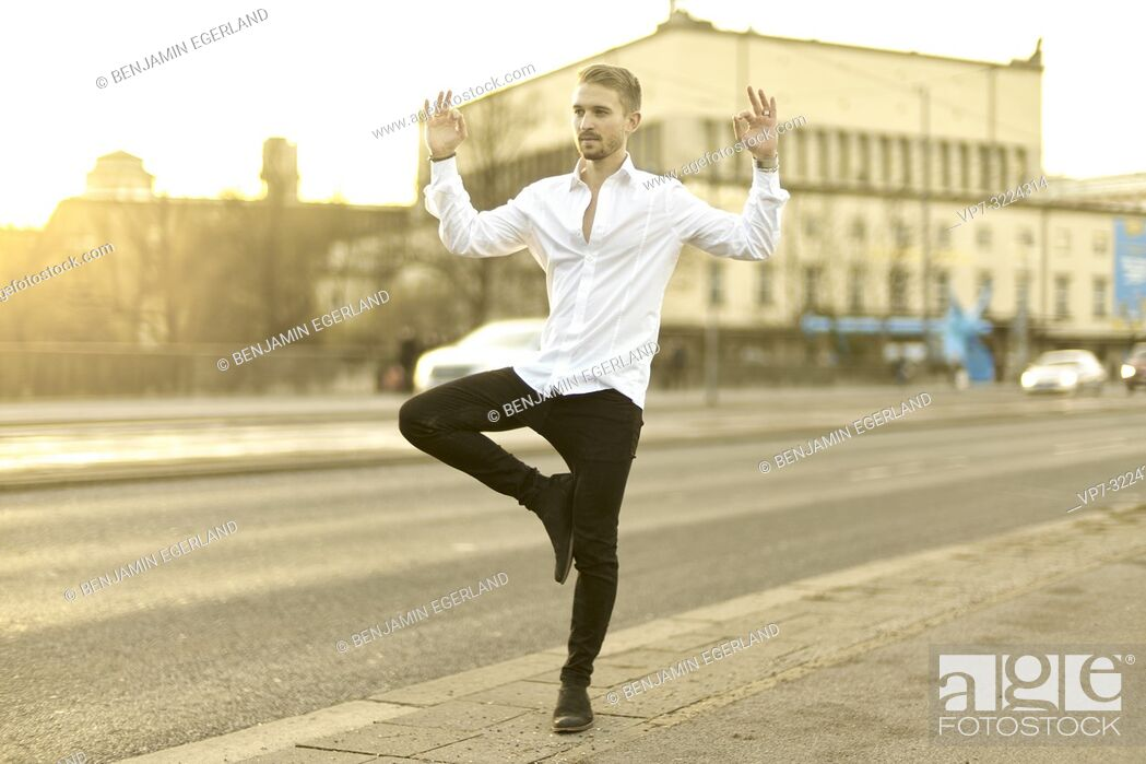 Stock Photo: calm relaxed young man balancing on one foot at street, meditating, in Munich, Germany.