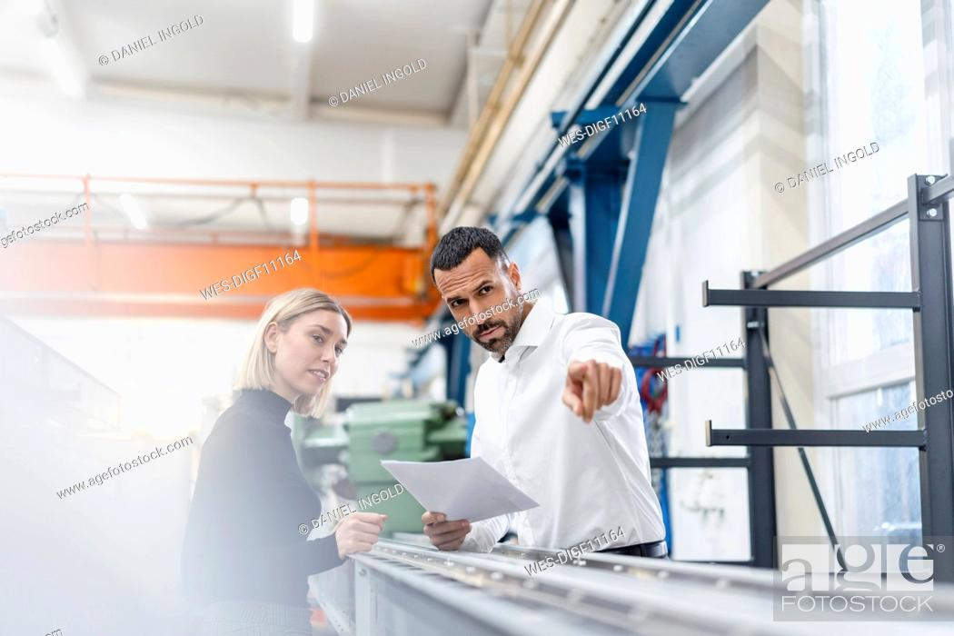 Stock Photo: Businessman and woman with papers examining metal rods in factory hall.