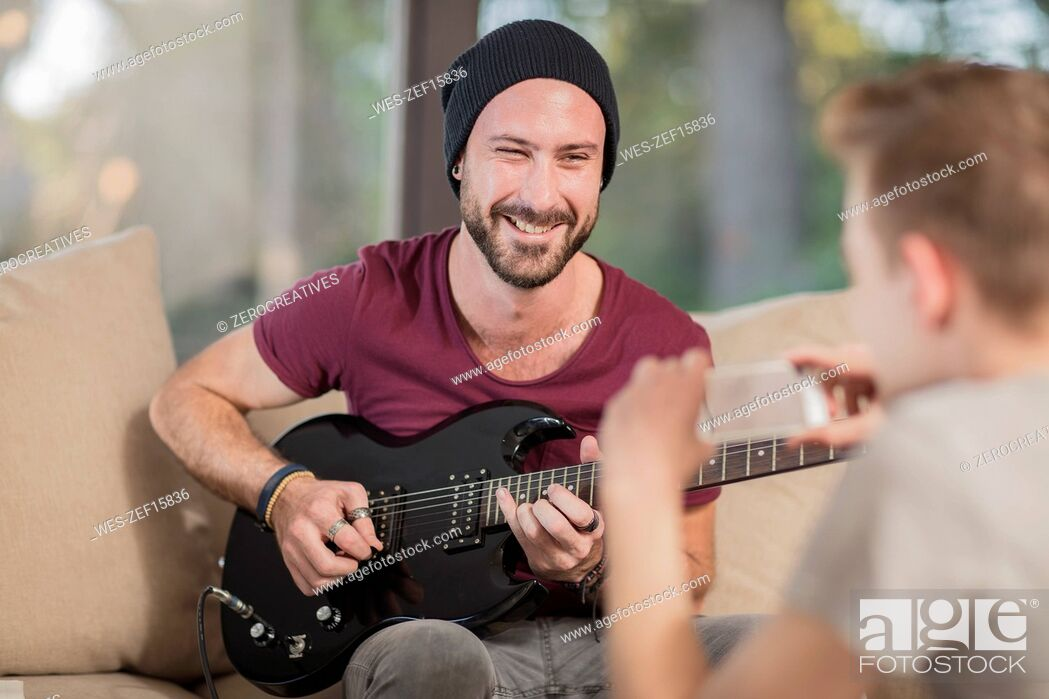 Stock Photo: Young man at home sitting on couch playing guitar for teenage boy taking a cell phone picture.