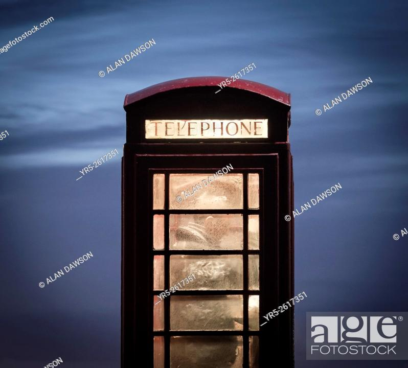 Stock Photo: Man making call from red telephone box at night. England, United Kingdom.