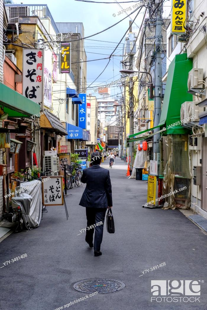Stock Photo: Businessman walks through a typical small street in Tokyo, Japan in summer 2019.