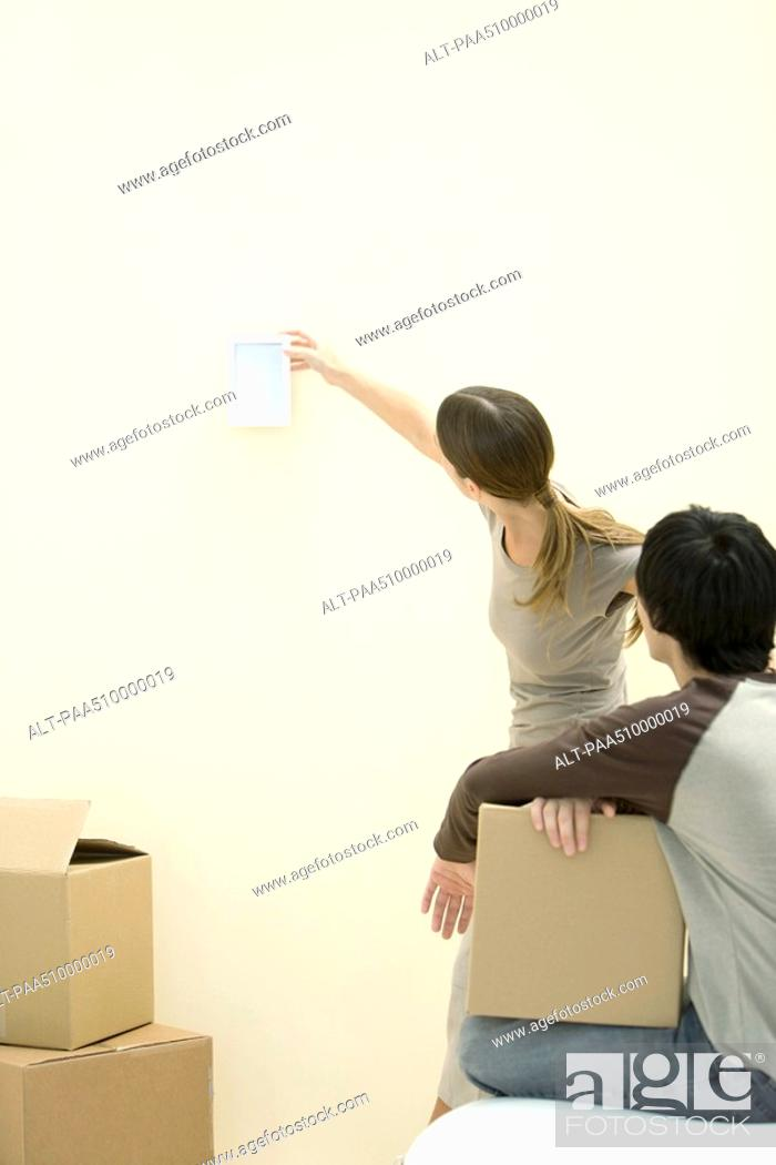 Stock Photo: Woman hanging picture frame on wall, man watching, holding cardboard box.