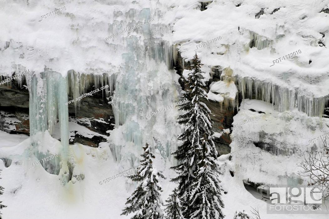 Stock Photo: Frozen waterfalls and icicles by mountain side.