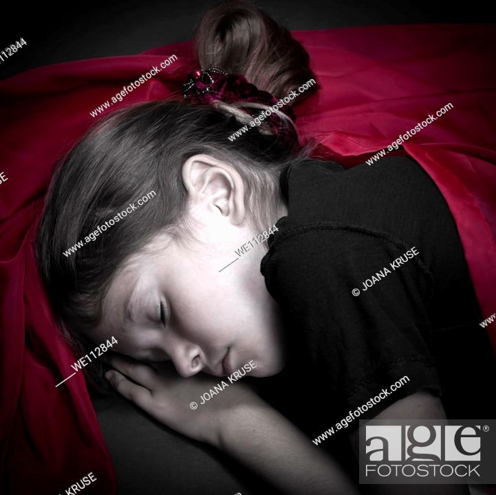 Stock Photo: a girl is curled up asleep in a red cloth.