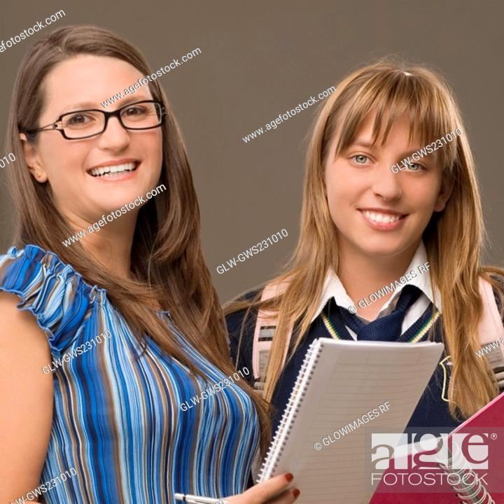 Stock Photo: Portrait of a teenage girl standing with her female teacher and smiling.
