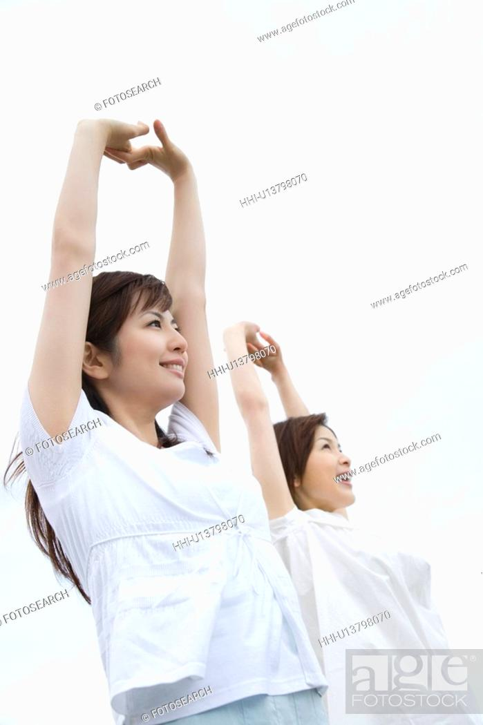 Stock Photo: Two young women under the sky, stretching arms above head, low angle view.