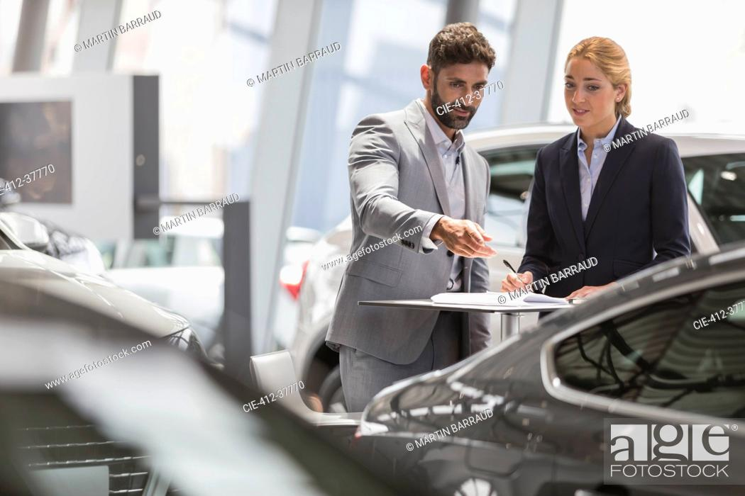Photo de stock: Car sales people meeting, examining new car in car dealership showroom.
